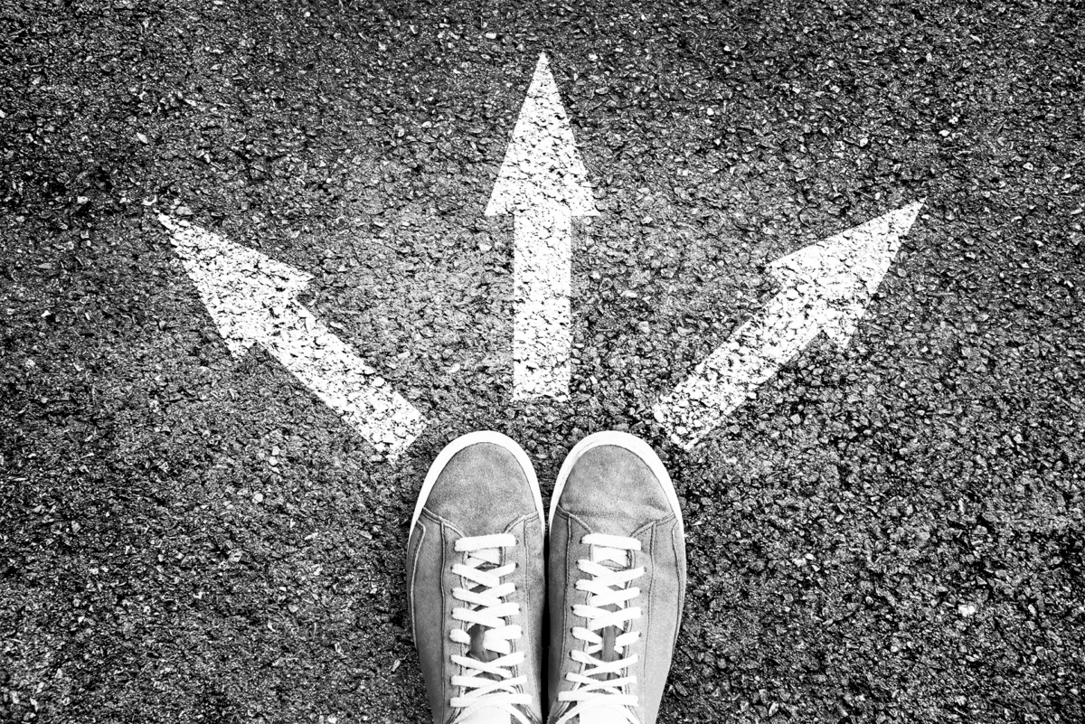 shoes and arrows pointing in different directions on asphalt floor 1